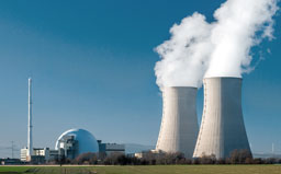 Nuclear power station countryside with two steaming cooling towers and blue sky