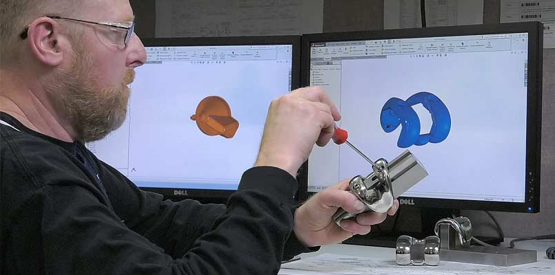 Engineer working on implant assembly, CAD drawing of implant on monitor