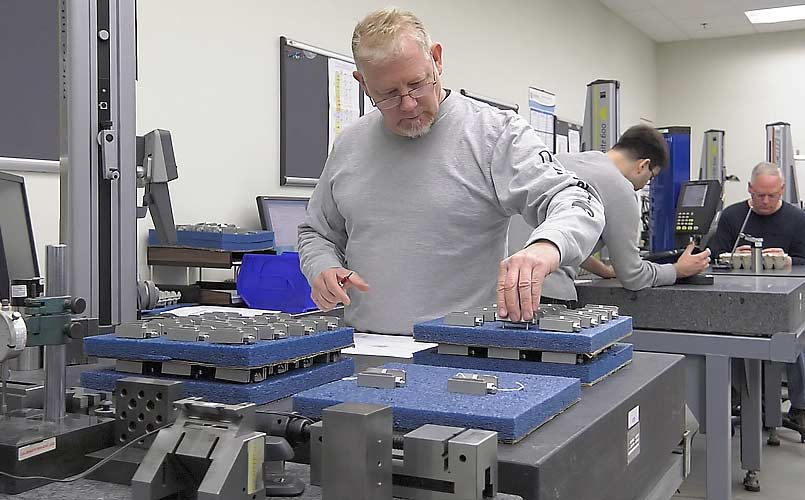Technician inspecting robotics parts manufacturing quality control