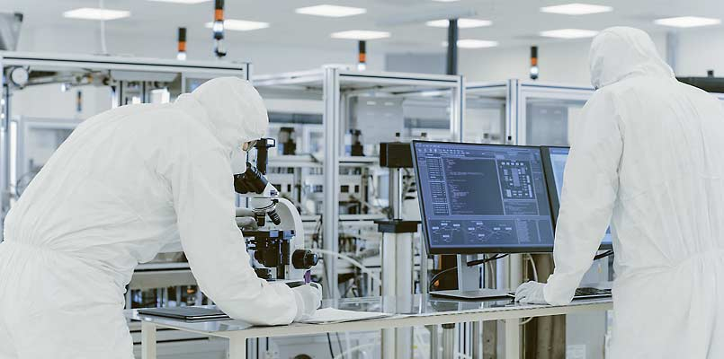 Semiconductor production technicians in lab wearing protective gear